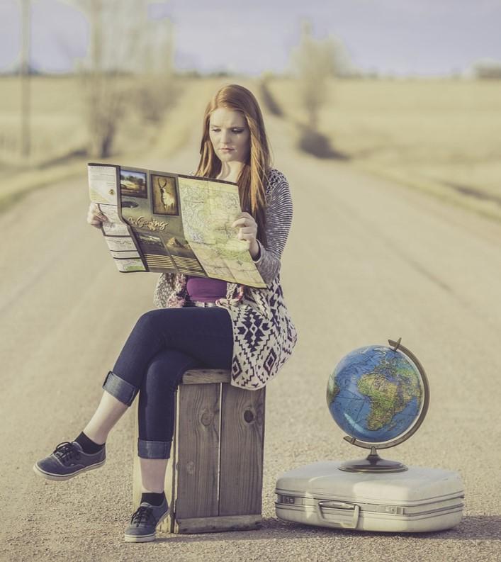 Devojka sedi sama sa koferom na ulici i gleda u kartu